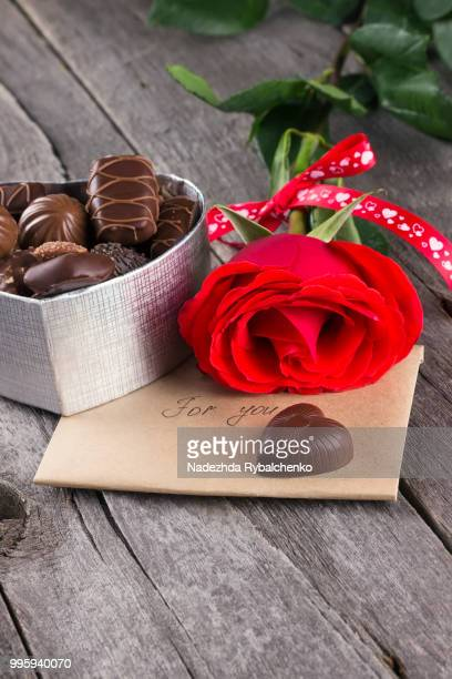 box of chocolates, red rose on a dark background - animal internal organ stock photos and pictures