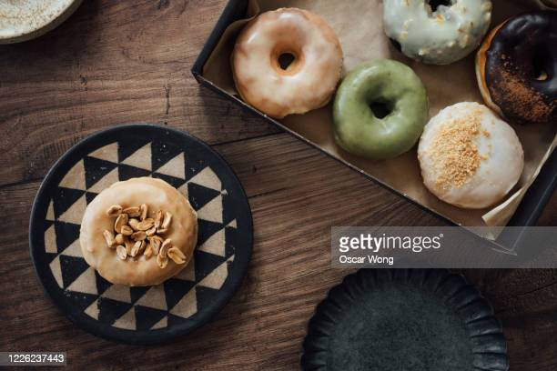 a box of delicious crafted donuts for sharing - ドーナツ ストックフォトと画像
