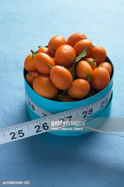 box of kumquats with measuring tape around them - heidi coppock beard fotografías e imágenes de stock