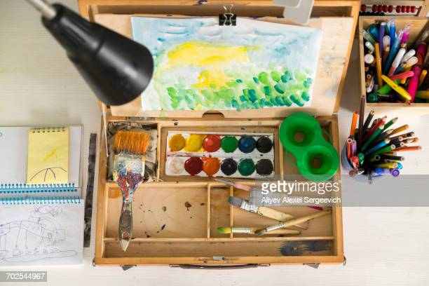 Box of paint, paintbrushes, drawing and assortment of colour pencils and painting tools