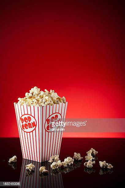 Box of popcorn on reflective surface and red background