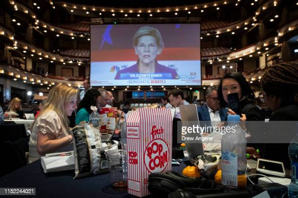 A box of popcorn sits next to reporters as they watch Democratic presidential candidate and US Senator Elizabeth Warren on a monitor inside the spin...
