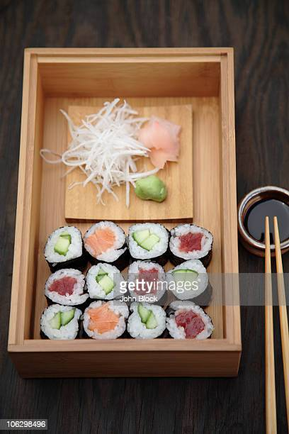 box of sushi rolls and soy sauce - dikon radish stock photos and pictures