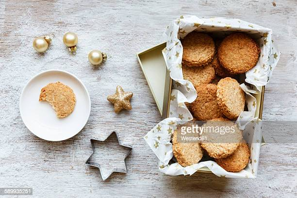 Box of whole grain cocos cookies, Christmas decoration and cookie cutter on wood