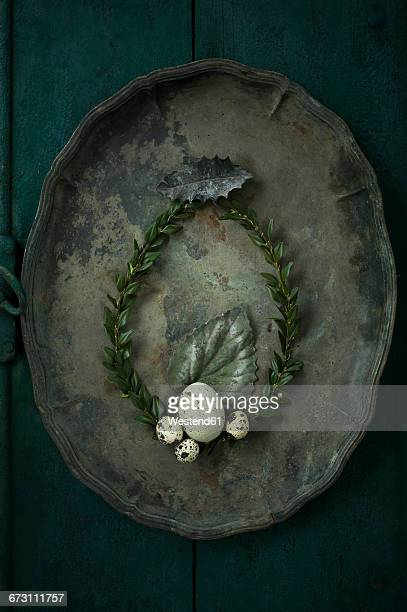Box tree wreath, goose egg and quail eggs on an old metal tray