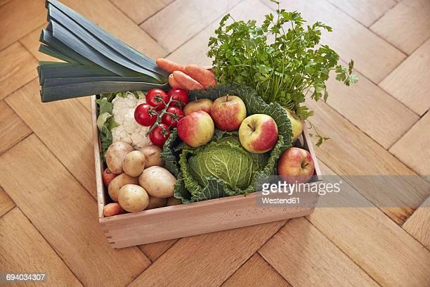 Box with produce on parquet floor