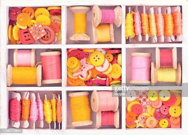 box with sewing set collection of yellow, red, pink spools threads arranged in a white wooden box - button sewing item stock pictures, royalty-free photos & images