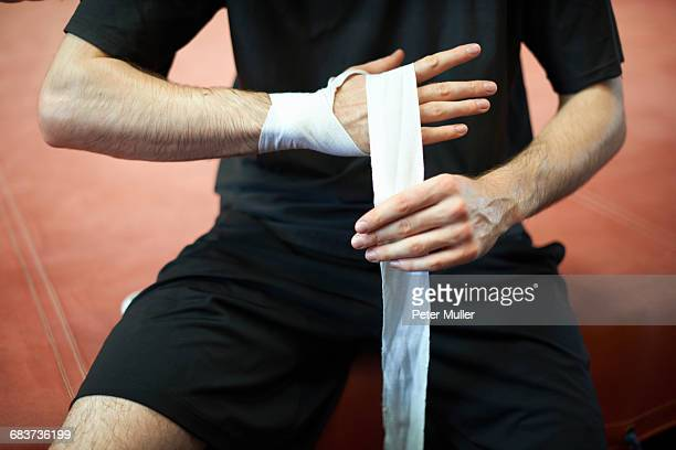 Boxer bandaging hands before putting on gloves, mid section