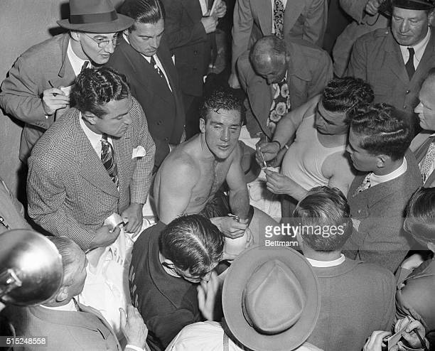 Boxer Billy Conn in his dressing room, surrounded by waiters after losing a rematch with Joe Louis.