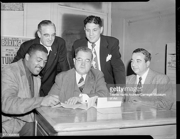 Boxer Bob Baker signing contract surrounded by TW Stephen Anthony 'Cowboy' DeLuca William Bettor and another man in office Pittsburgh Pennsylvania...