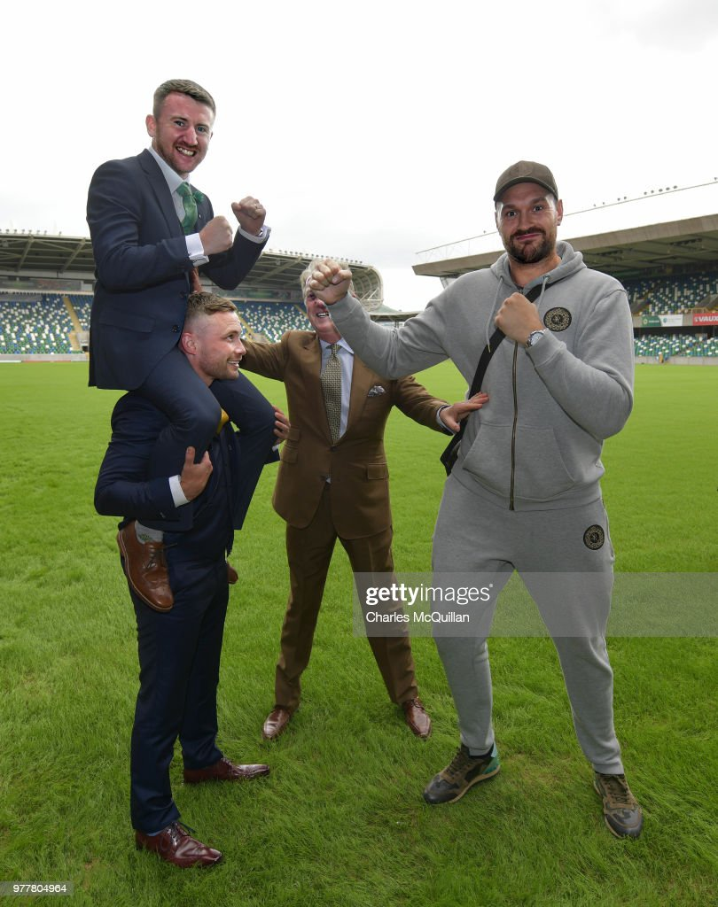 Boxer Carl Frampton gives friend and fellow boxer Paddy Barnes a leg up as he goes toe to toe with Tyson Fury watched by promoter Frank Warren as they attend a photo call at Windsor Park on June 18, 2018 in Belfast, Northern Ireland. The three boxers held a press conference earlier to announce their August Frank Warren boxing bill at the home of Northern Ireland football.