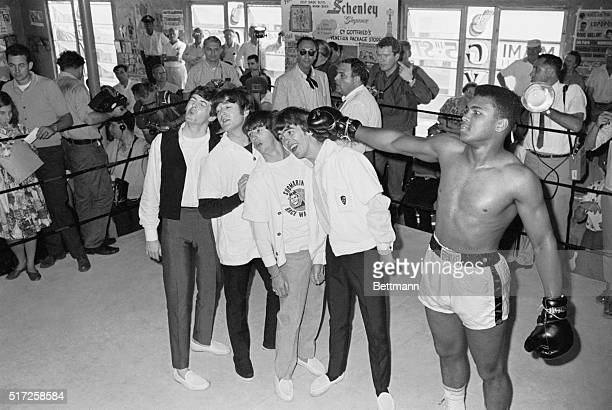 Boxer Cassius Clay later known as Muhammad Ali playfully hits The Beatles while at his training camp From left to right Paul McCartney John Lennon...