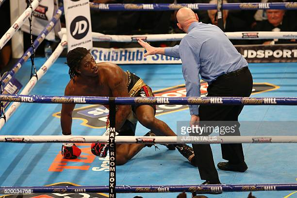 US boxer Charles Martin gets back up onto his feet to continue fighting after he was knocked down by British boxer Anthony Joshua during their IBF...