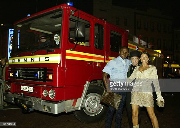 Boxer Chris Eubank and two unidentified people arrive by a fire truck to the Twin Towers celebrity party held at Red Cube September 8 2002 in London...