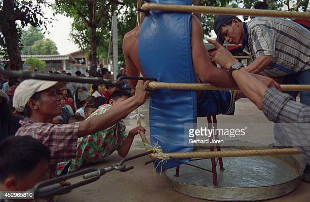 A boxer draws breath between rounds at a bareknuckle fight between a Thai and a Burmese at a temple in Mae Kon Ken village close to the ThaiBurmese...