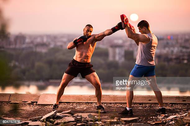 Boxer exercising at sunset with his personal sports trainer.