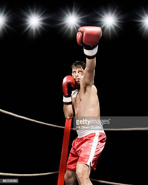 Boxer extending arm in boxing ring