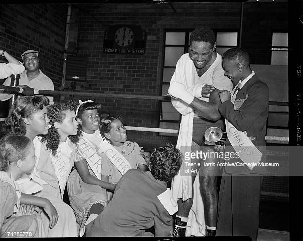 Boxer Ezzard Charles showing muscles to children wearing 'Cheers for Charles' sashes including Ethel Holt Jacqueline Holyfield Chestina Mallory...