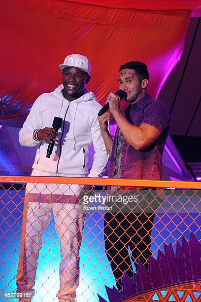Boxer Floyd Mayweather Jr and actor Carlos PenaVega speak onstage during Nickelodeon Kids' Choice Sports Awards 2014 at UCLA's Pauley Pavilion on...