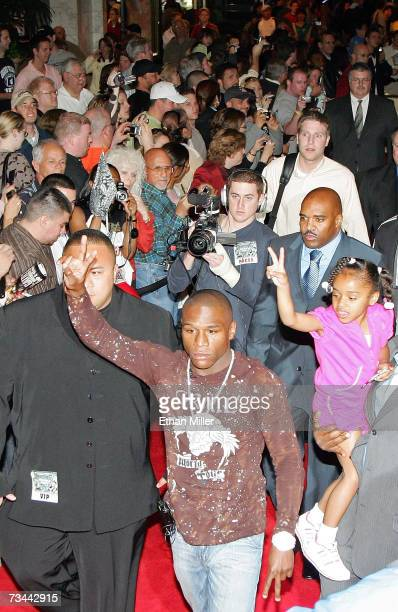 Boxer Floyd Mayweather Jr and his daughter Iyanna Mayweather signal to fans as he arrives for a news conference at the MGM Grand Hotel/Casino as part...