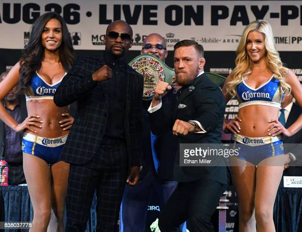 Boxer Floyd Mayweather Jr and UFC lightweight champion Conor McGregor pose as Mayweather Promotions CEO Leonard Ellerbe looks on during a news...