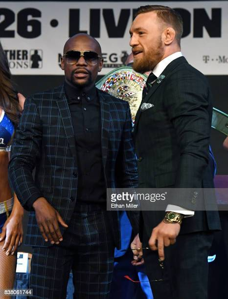 Boxer Floyd Mayweather Jr and UFC lightweight champion Conor McGregor prepare to pose during a news conference at the KA Theatre at MGM Grand Hotel...