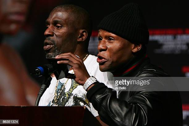 Boxer Floyd Mayweather Jr answers questions as he stands with his uncle/trainer Roger Mayweather during a news conference announcing his return to...