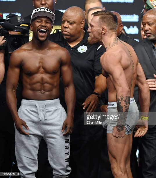 Boxer Floyd Mayweather Jr. Laughs after facing off with UFC lightweight champion Conor McGregor during their official weigh-in at T-Mobile Arena on...