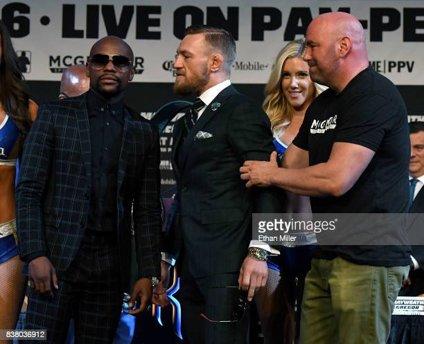 Boxer Floyd Mayweather Jr poses as UFC lightweight champion Conor McGregor is pulled back by UFC President Dana White during a news conference at the...