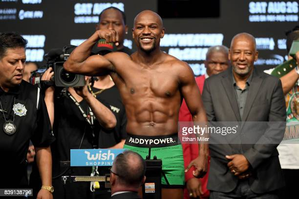 Boxer Floyd Mayweather Jr poses on the scale during his official weighin at TMobile Arena on August 25 2017 in Las Vegas Nevada Mayweather will meet...