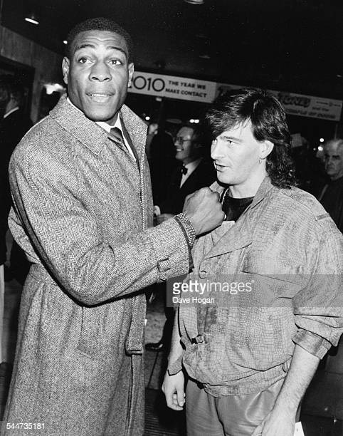 Boxer Frank Bruno pretending to punch football player Charlie Nicholas on the chin at the premiere of the movie 'Beverly Hill Cop' in London January...