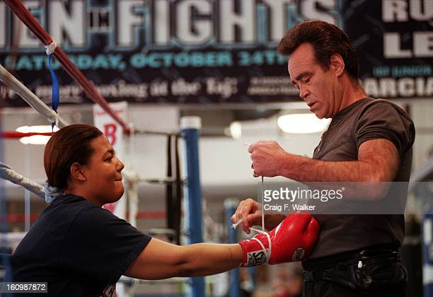 Boxer Freeda Foreman daughter of former heaveyweight champion George Foreman puts her gloves on with trainer Larry Goossen before working out at...