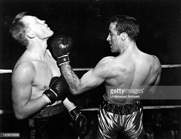 A boxer greets his opponent with a sharp uppercut to the jaw early to mid 1950s