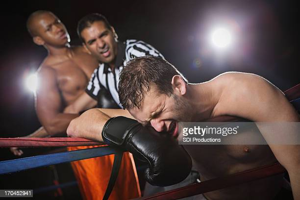 boxer grimacing after losing fight to competitor - combat sport stock pictures, royalty-free photos & images