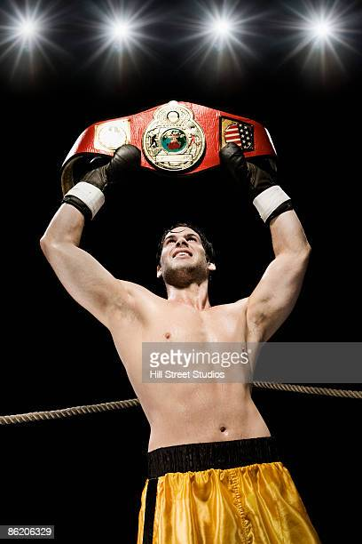 Boxer holding championship belt overhead in boxing ring
