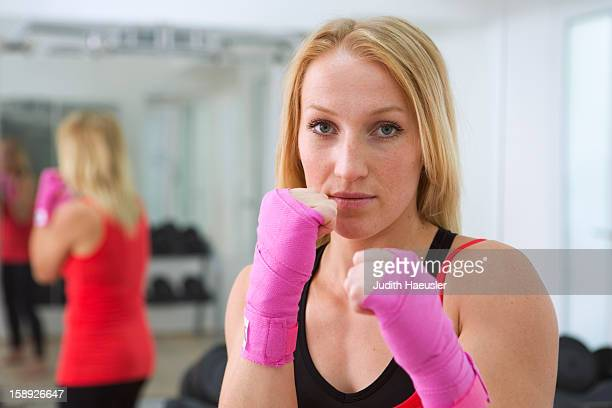 Boxer holding fists up in gym
