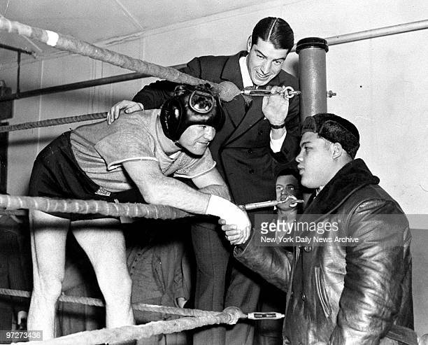 Boxer James Braddock shakes hands with Joe Louis while baseball great Joe DiMaggio looks on Braddock is training for his next fight