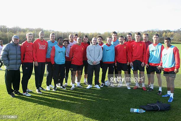 Boxer Jamie Moore poses with manager Sir Alex Ferguson and the Manchester United football squad during a first team training session at Manchester...