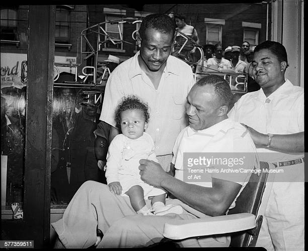 Boxer 'Jersey' Joe Walcott with baby on lap getting haircut from barber Clarence 'Speedy' Williams in Crystal Barber Shop Pittsburgh Pennsylvania...