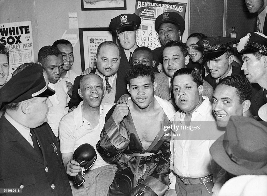 Boxer Joe Louis, center, flanked by his trainer, Jack Blackburn (left), and his manager, Julian Black, shows the fist that won him the heavyweight crown over James Braddock in the eight round of their fight in Chicago. June 22, 1937.