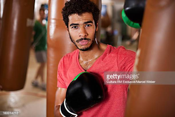 Boxer leaning on punching bag in gym