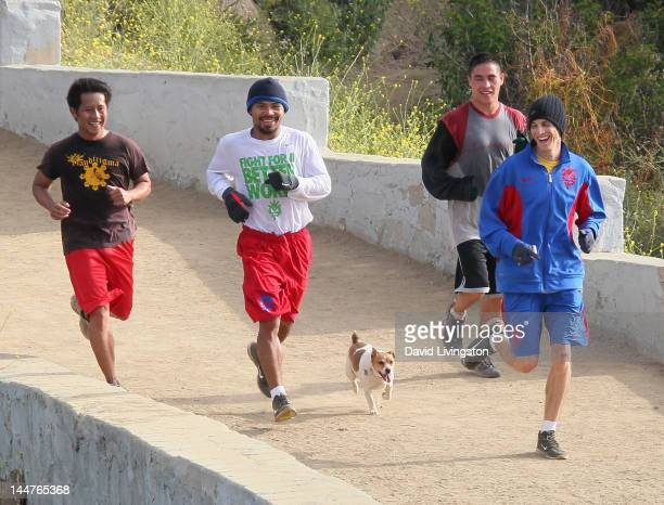Boxer Manny Pacquiao and Brian Livingston train with Pacquiao's dog Pacman in Griffith Park on May 18 2012 in Los Angeles California