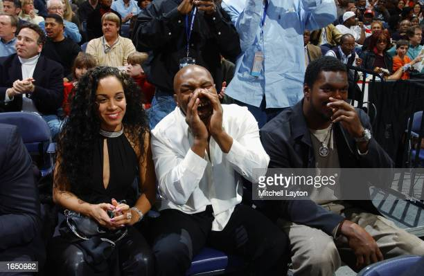 Boxer Mike Tyson cheers alongside football player LaVar Arrington during the game between the Los Angeles Lakers and the Washington Wizards at the...