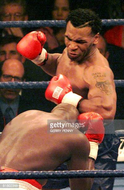 US boxer Mike Tyson knocks down Britain's Julius Francis during the first round of their Heavyweight bout 29 January 2000 at the Manchester Arena