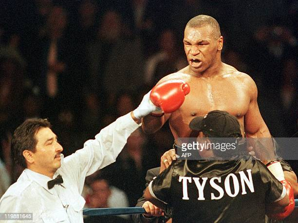 Boxer Mike Tyson of the United States exhorts Andrew Golota of Poland to continue fighting as referee Frank Garza Jr. Raises his hand awarding him a...