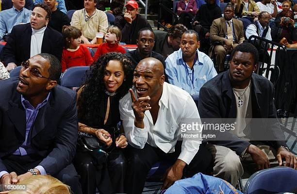 Boxer Mike Tyson sits with Ray Lewis and LaVar Arrington watch the game between the Los Angeles Lakers and the Washington Wizards during the game at...