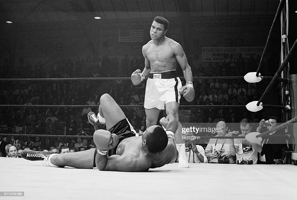 Boxer Muhammad Ali stands over boxer Sonny Liston after knocking him down during the first round of their match. Clay won the May 25, 1965 fight and retained his title as heavyweight champion.