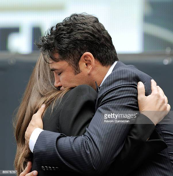 Boxer Oscar De La Hoya hugs his wife Millie Corretjer after announcing his retirement from boxing on April 14 2009 at Staples Center in Los Angeles...