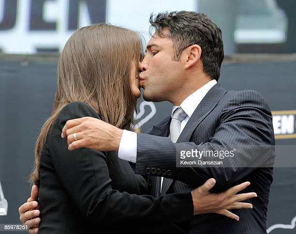Boxer Oscar De La Hoya kisses his wife Millie Corretjer after announcing his retirement from boxing on April 14 2009 at Staples Center in Los Angeles...