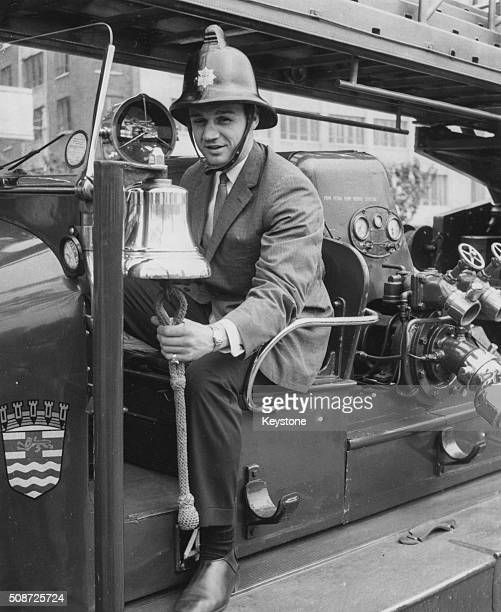Boxer Paul Pender World Middleweight Champion wearing a fireman's helmet and ringing the bell as he takes a ride on a fire engine during a visit to...